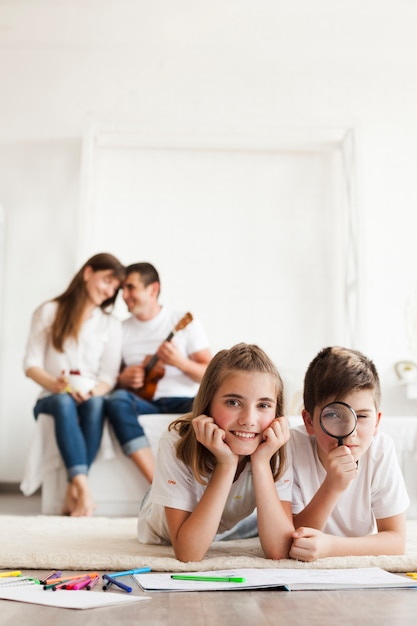 Smiling sibling lying on rug carpet looking at camera while their parent sitting on sofa Free Photo
