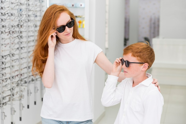 Smiling sibling with black eyeglasses posing in optics store Free Photo