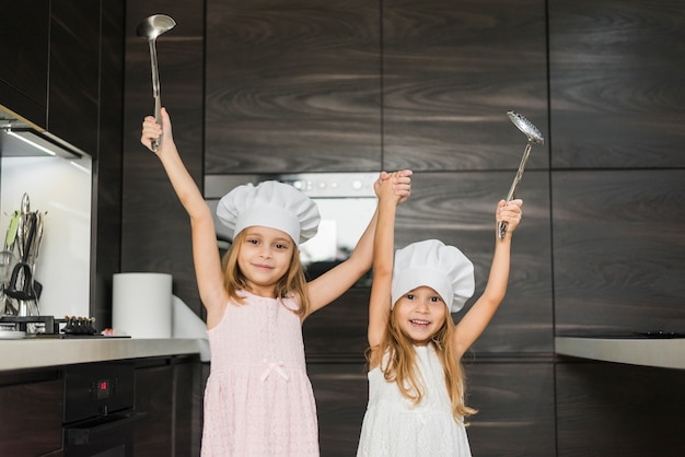 Smiling siblings with raised hands in kitchen holding ladle Free Photo