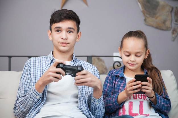 Smiling siblings with smartphone and controller Free Photo