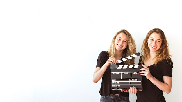 Smiling sister holding clapperboard against white background Free Photo