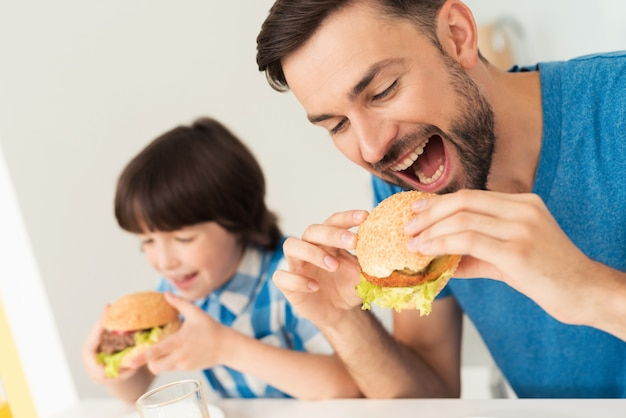 Smiling son and father have lunch in kitchen. Premium Photo