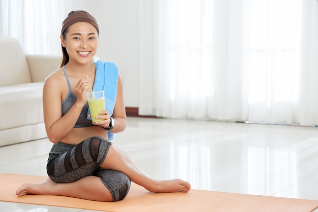 Smiling sportswoman with glass of smoothie Free Photo