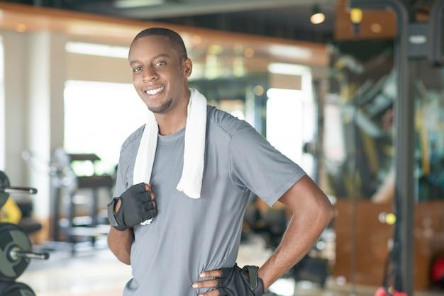Smiling sporty black man wearing towel around neck Free Photo