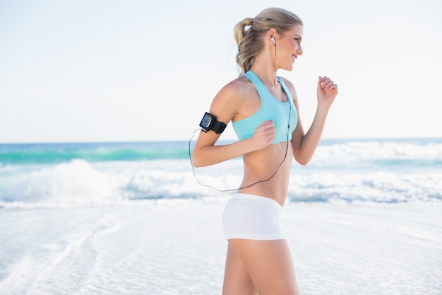 Smiling sporty blonde in sportswear jogging Premium Photo