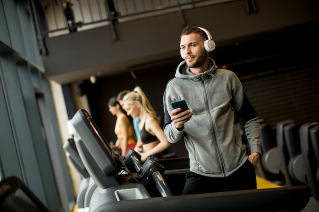 Smiling sporty man listening to music in gym Premium Photo
