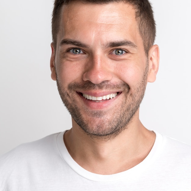 Smiling stubble young man in white t-shirt against plain wall Free Photo