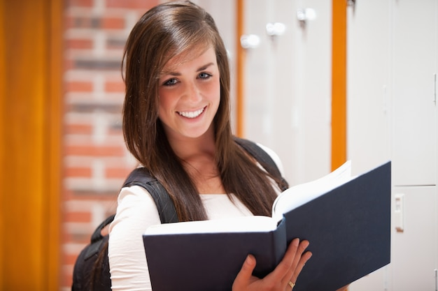 Smiling student holding a book Premium Photo