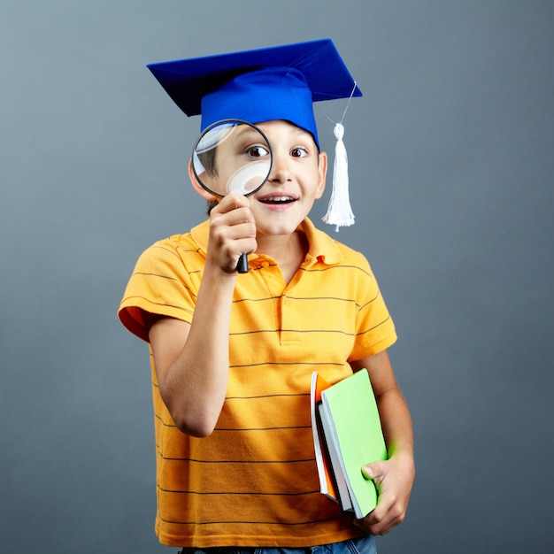 Smiling student playing with his magnifying glass Free Photo
