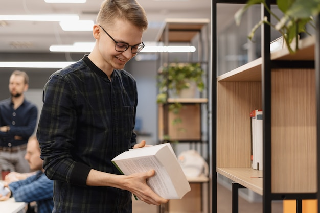 Uno studente sorridente con un libro tra le mani Foto Gratuite