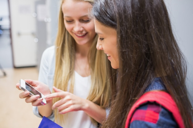 Smiling students using smartphone at university Premium Photo