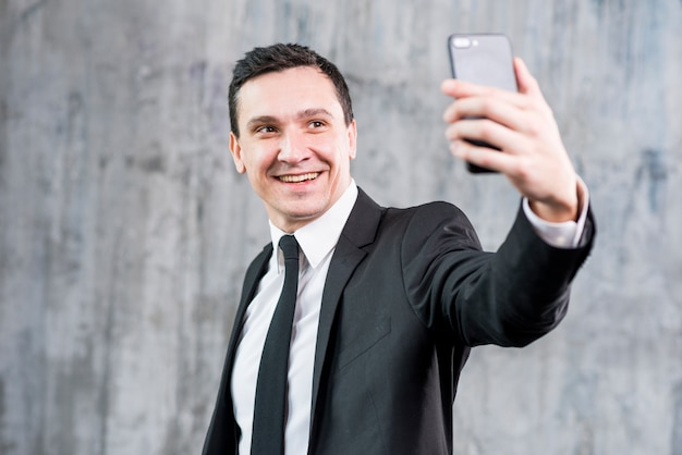 Smiling stylish businessman taking selfie with smartphone Free Photo