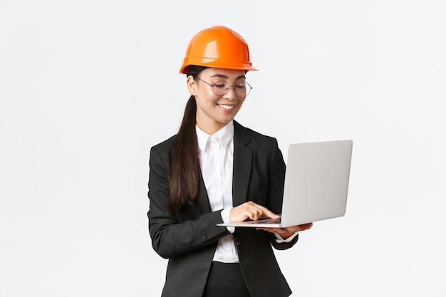성공적인 여성 아시아 산업 엔지니어, 안전 헬멧 공장 관리자 미소 프리미엄 사진