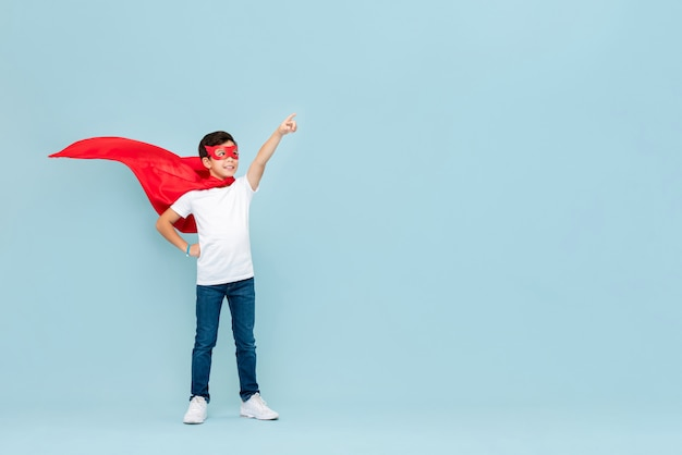Smiling superhero boy in red mask and cape pointing hand aside Premium Photo