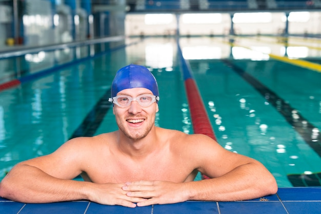 Smiling swimmer siting on edge of pool Free Photo