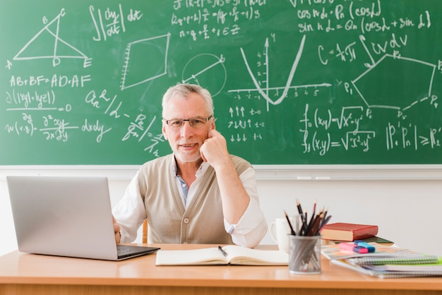 Smiling teacher near laptop in lecture room Free Photo