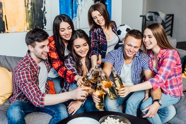 Smiling team of workers after job relaxed at home with beer. Premium Photo