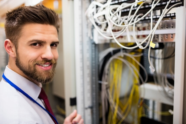Smiling technician standing in a server room Premium Photo