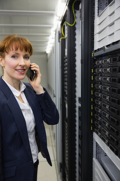 Smiling technician talking on phone while looking at server Premium Photo