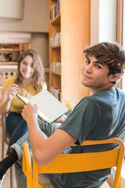 Smiling teen boy with book sitting near girlfriend 23 2147860605