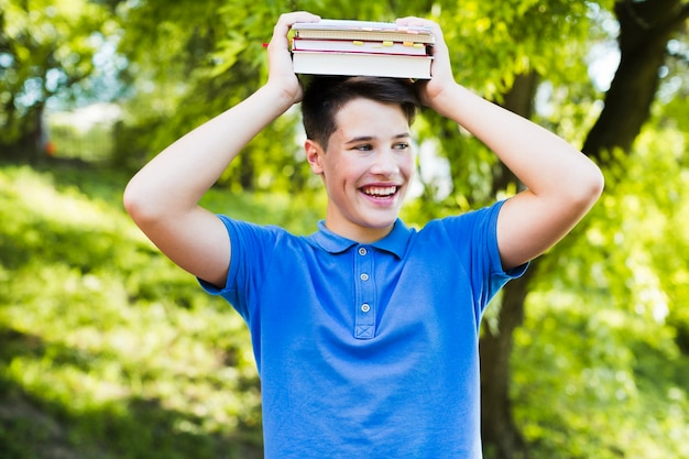 Smiling teen boy with books Free Photo
