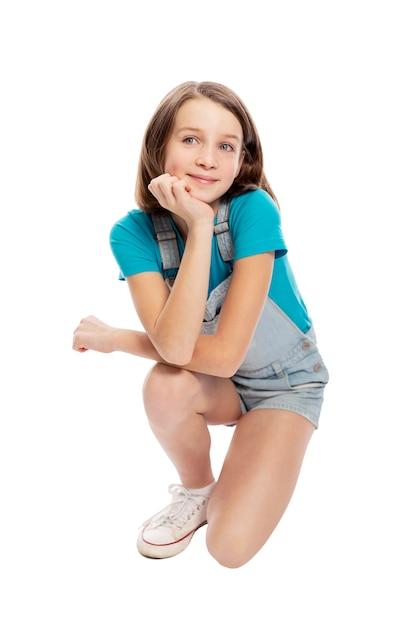 Smiling teen girl in denim overalls squats. isolated on a white background Premium Photo