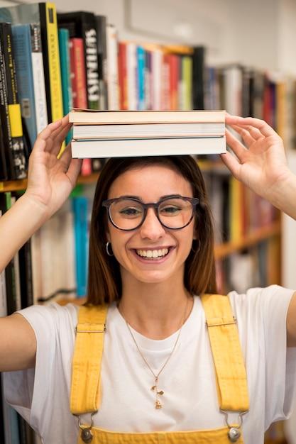 Smiling teen schoolgirl with books on head Free Photo
