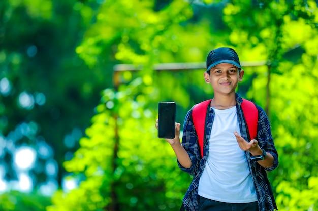 Улыбающийся мальчик-подросток в синей рубашке показывает смартфон с пустым экраном Premium Фотографии