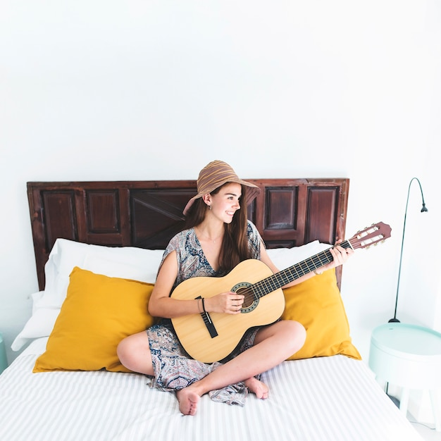 Smiling teenage girl sitting on bed playing guitar in bedroom Free Photo