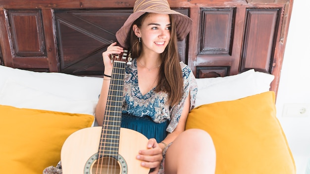 Smiling teenage girl sitting on bed with guitar Free Photo