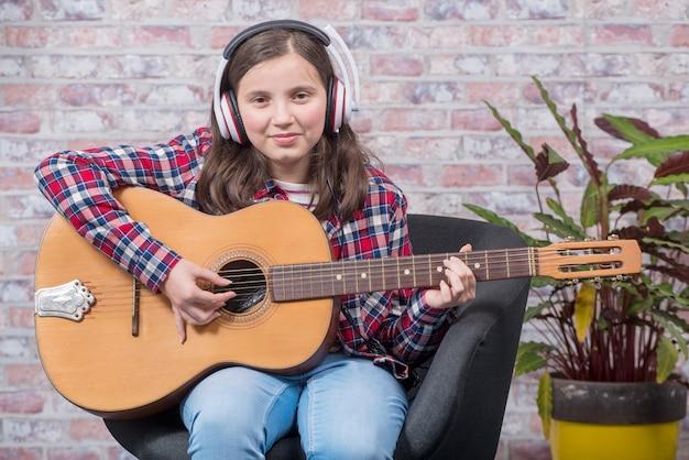 Smiling teenager girl  playing guitar Premium Photo