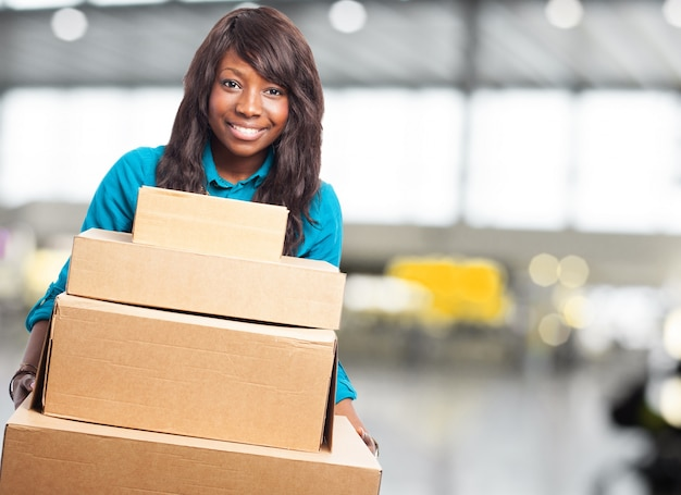 Smiling teenager holding cardboard boxes Free Photo