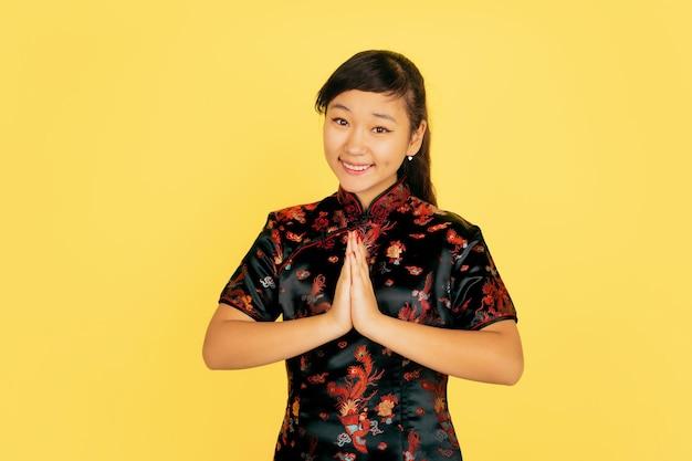 笑顔、かわいいありがとう。旧正月おめでとう。黄色の背景にアジアの若い女の子の肖像画。伝統的な服を着た女性モデルは幸せそうに見えます。お祝い、人間の感情。コピースペース。 無料写真