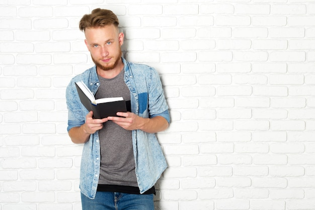 Smiling and thoughtful casual man reading a book Premium Photo