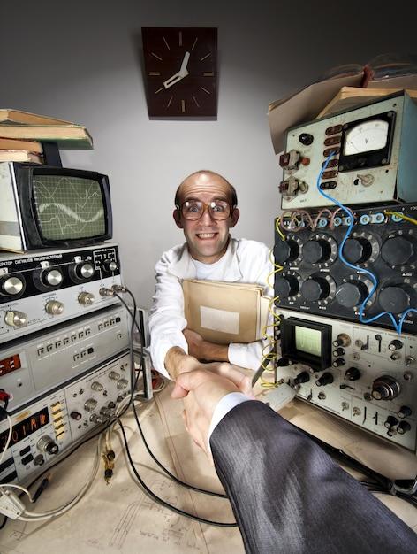 Улыбающийся робкий ученый, пожимая руку бизнесмена Premium Фотографии
