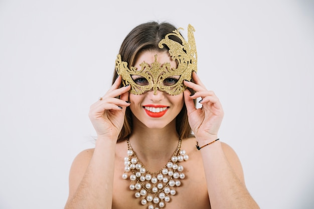 Smiling topless woman wearing golden decorative carnival mask and necklace Free Photo