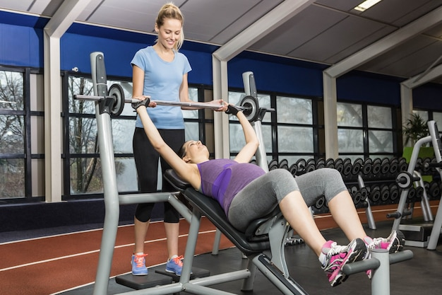 Smiling trainer helping pregnant woman lifting barbell at the gym Premium Photo