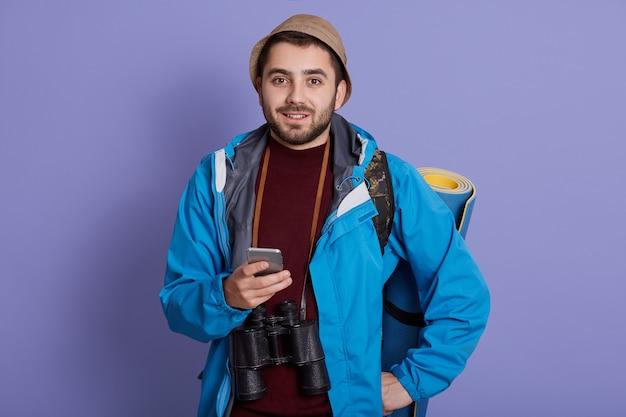 キャップとバックパックで旅行者の男の笑みを浮かべてください。週末の休暇に旅行する、気分が良い、スマートフォンを持っている観光客 無料写真