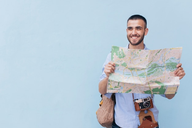 Smiling traveler photographer holding map and looking away standing against blue backdrop Free Photo