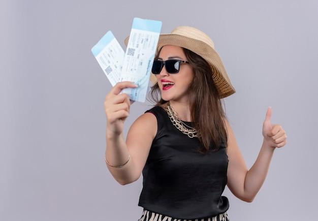 Улыбающаяся молодая девушка путешественника в черной майке в шляпе в gkasses держит билеты большим пальцем вверх на белом фоне Бесплатные Фотографии
