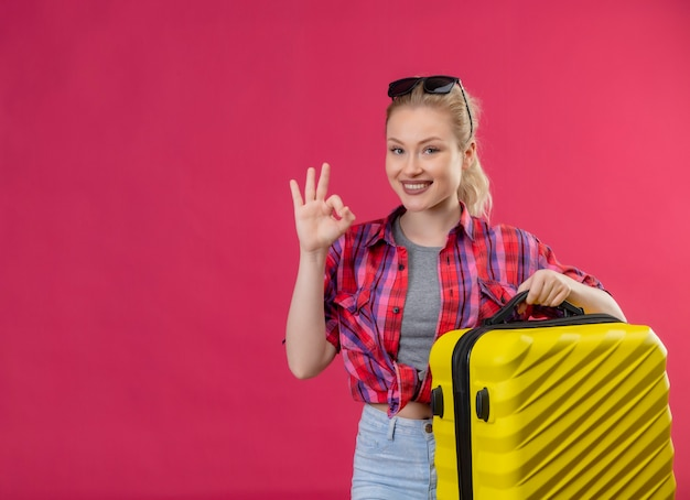 Smiling traveler young girl wearing red shirt holding suitcase shows oker gesture on isolated pink background Free Photo