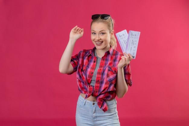 Улыбающаяся молодая девушка путешественника в красной рубашке в очках с билетами показывает размер на изолированном розовом фоне Бесплатные Фотографии