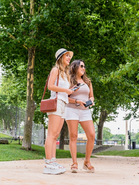 Smiling two female tourist standing in the park holding map and camera Free Photo