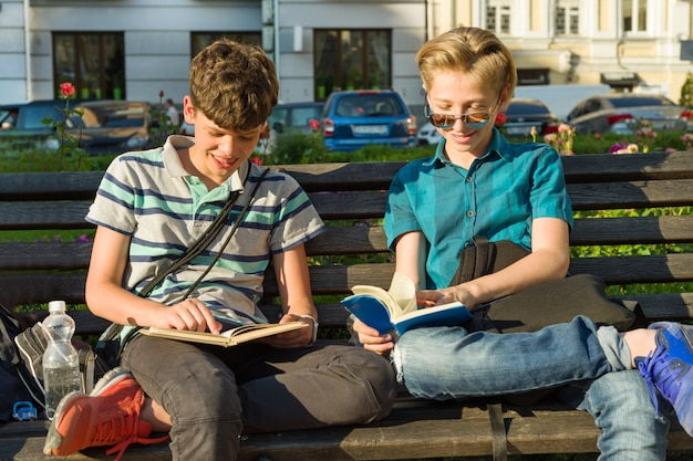 Smiling two schoolboys reading books Premium Photo