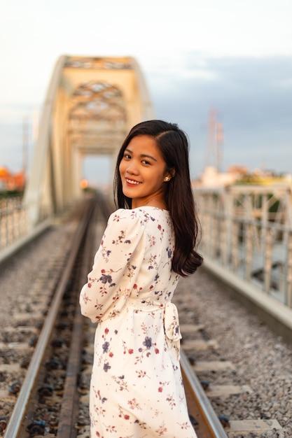 Sorridente donna vietnamita con i capelli neri in piedi su un vecchio ponte Foto Gratuite