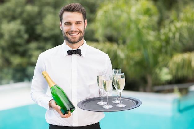 シャンパンフルートとボトルを保持している笑顔のウェイター Premium写真