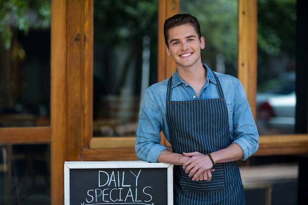 카페 외부 메뉴 보드에 기대어 웨이터 미소 프리미엄 사진