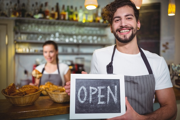 Smiling waiter showing slate with open sign in café Free Photo