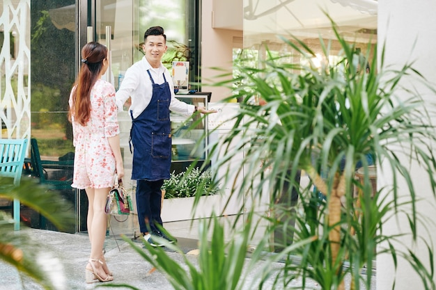 카페에서 예쁜 젊은 여자를 환영하고 그녀를 위해 문을 여는 웨이터 미소 프리미엄 사진