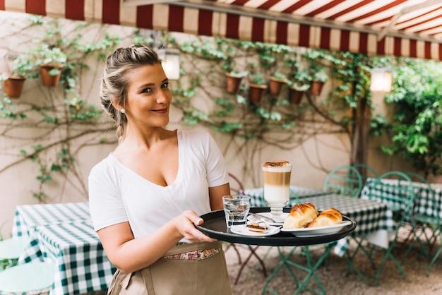 Smiling waitress holding tray Free Photo